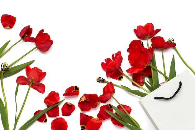 Сломанные старые красные тюльпаны в подарочной сумке на белом