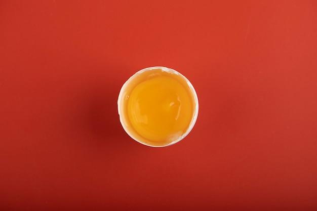 Broken organic egg on red surface.
