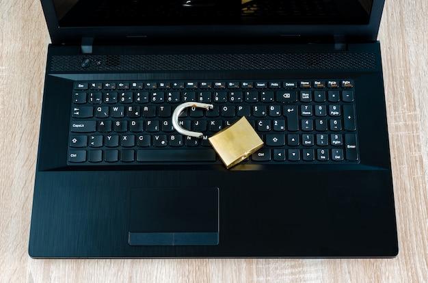 Сломанный замок на открытом ноутбуке, нарушение концепции безопасности интернета и технологии или кража данных