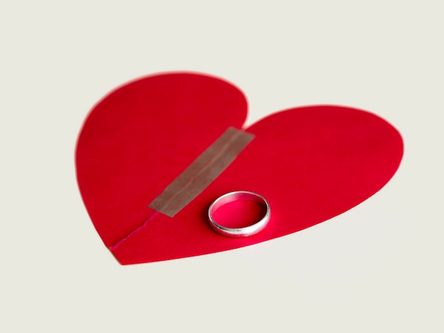 Broken paper heart with marriage ring