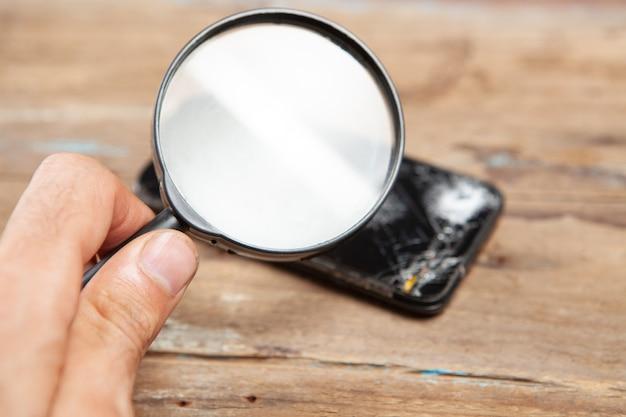 Сломанный телефон и увеличительное стекло на деревянном столе. лупа смотрит на сломанный телефон. поиск ремонта телефона