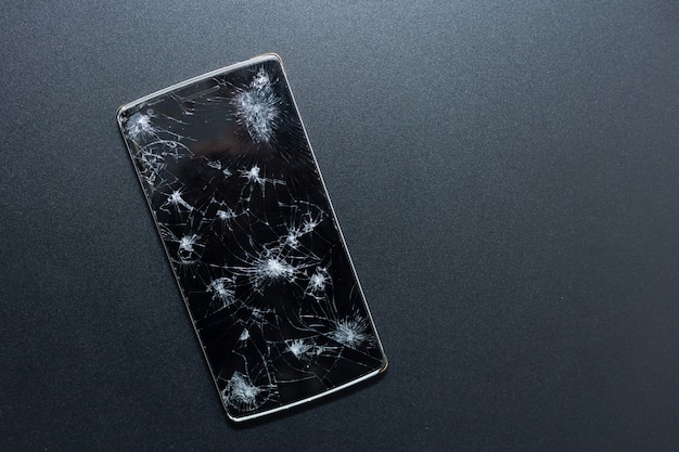 A broken phone on black background. crushed device with broken screen representing an accident. textured screen with damage. dark glass of a screen, broken.