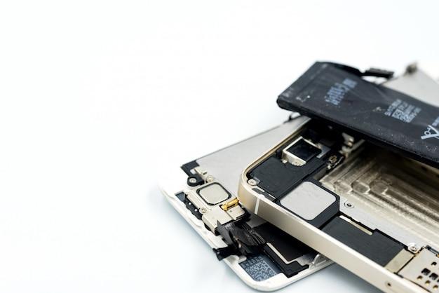 Сломанный телефон, запчасти, батарея разряжена, сотовый телефон на белом фоне