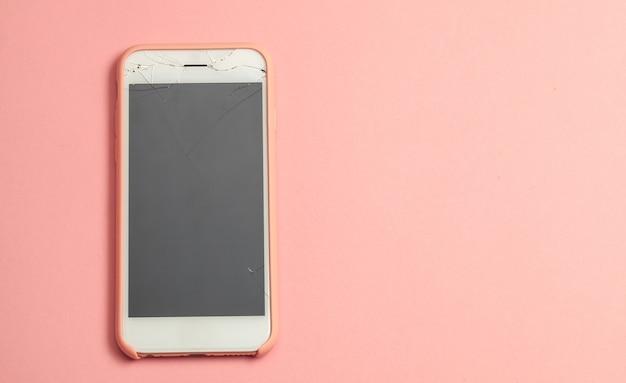 ピンクの背景のディスプレイガラスに亀裂のある壊れた電話。テキスト用のスペースをコピーします。