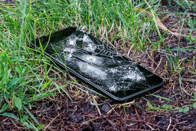 Broken phone with hole from bullet in grass