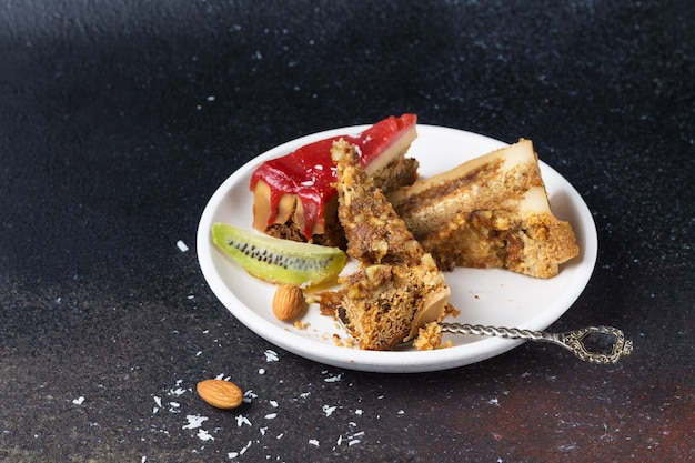 Разбитые куски торта с клубничной глазурью, кокосовой стружкой и миндалем на белой тарелке, крупный план