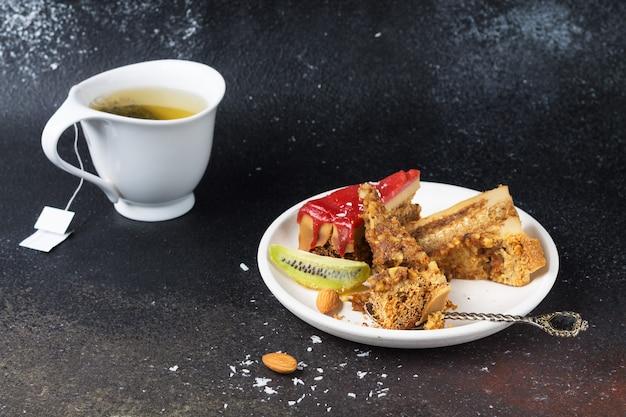 Разбитые куски торта с клубничной глазурью, кокосовой стружкой и миндалем на белой тарелке и чашке зеленого чая