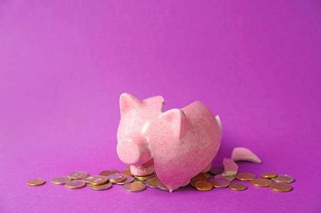Сломанная копилка и монеты на фиолетовом