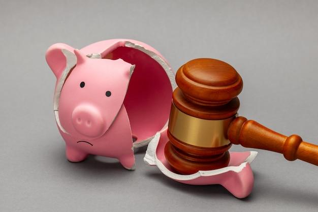 깨진 돼지 저금통과 회색 배경에 판사 망치. 파산, 위기 개념입니다.