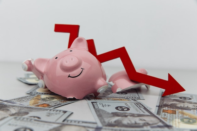 Сломанная копилка и красная стрелка вниз с долларовыми банкнотами. концепция инвестиций и банкротства.