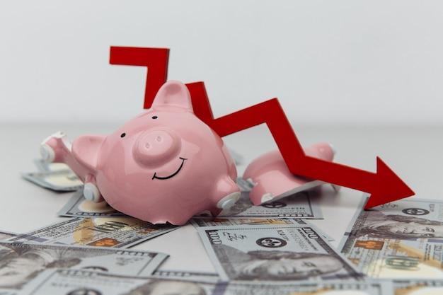 Сломанная копилка и красная стрелка с долларовыми банкнотами крупным планом, концепция инвестиций и банкротства