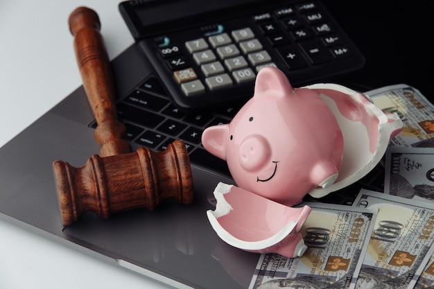 Broken piggy bank, cash and wooden gavel on keyboard. business and bankruptcy concept.