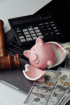 Broken piggy bank, dollar bills and gavel on keyboard. auction and bankruptcy concept. vertical image