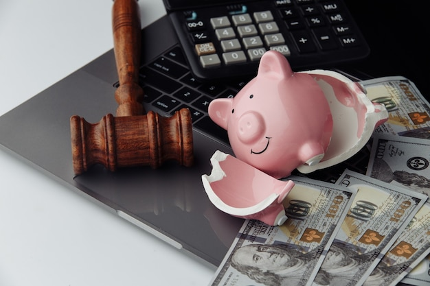 Broken piggy bank, dollar bills and gavel on keyboard. auction and bankruptcy concept