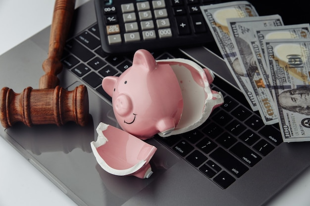Broken piggy bank, dollar bills and wooden gavel on laptop. auction and bankruptcy concept