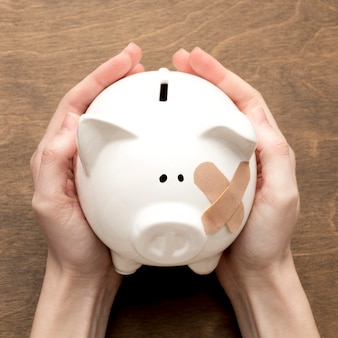 Broken piggy bank having band-aids
