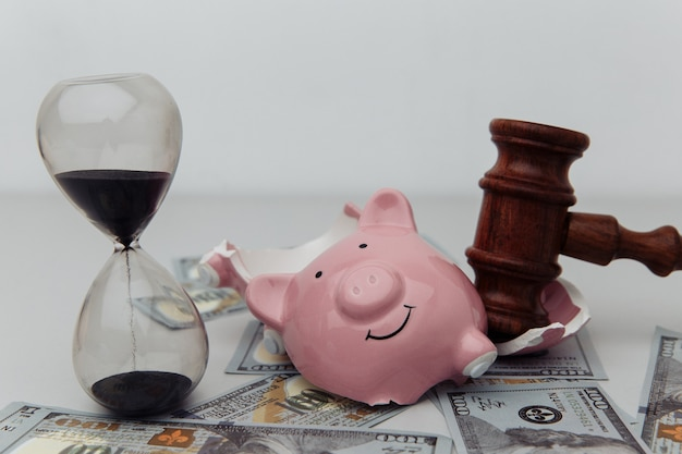 Broken piggy bank, hourglass and judge gavel.