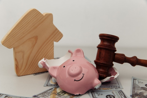 Broken piggy bank, house and judge gavel. bankruptcy or crisis concept.