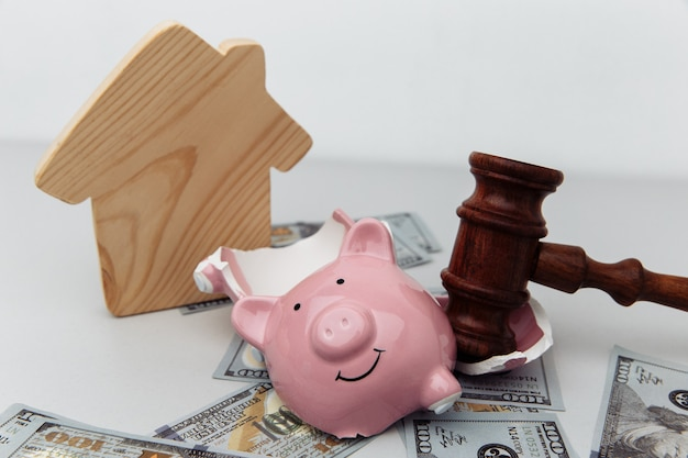 Broken piggy bank house and judge gavel bankruptcy and investment concept