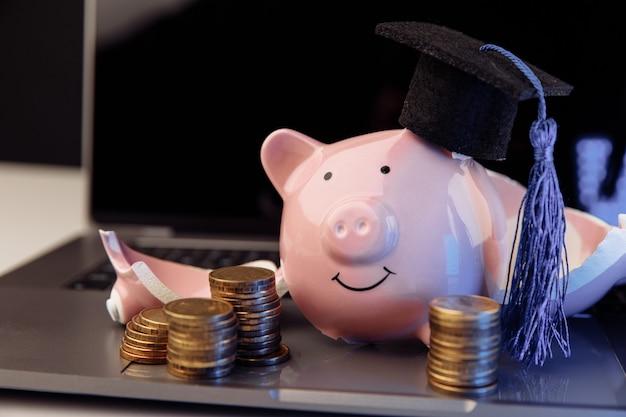 노트북에 모자에 깨진된 돼지 저금통입니다. 비싼 교육 개념입니다.