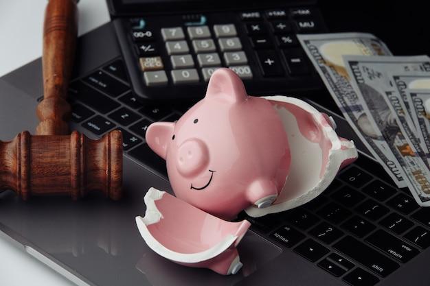 깨진 된 돼지 저금통, 돈 및 키보드 클로즈업에 나무 망치. 경매 및 파산 개념.