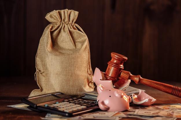 Разбитая копилка, мешок с деньгами и молоток судьи. концепция инвестиций и сбережений.