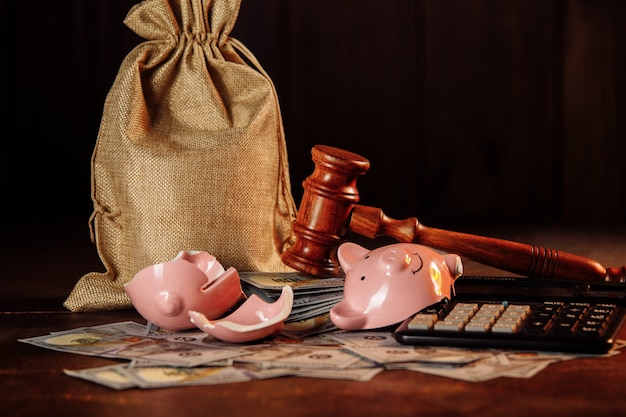 Broken piggy bank, money bag and judge gavel. investment and bankruptcy concept.