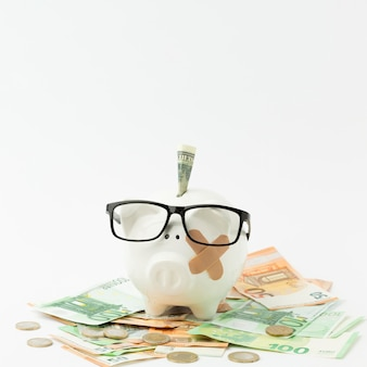 Broken piggy bank wearing glasses