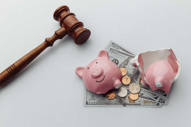 Broken piggy bank with cash and wooden gavel on a white