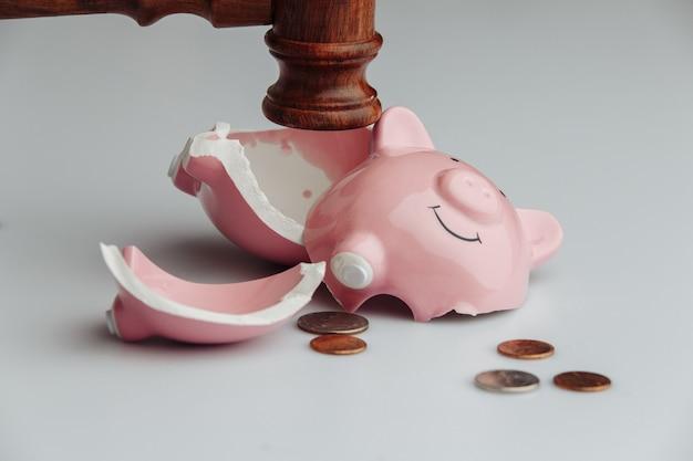 コインと木製の裁判官のガベルで壊れた貯金箱