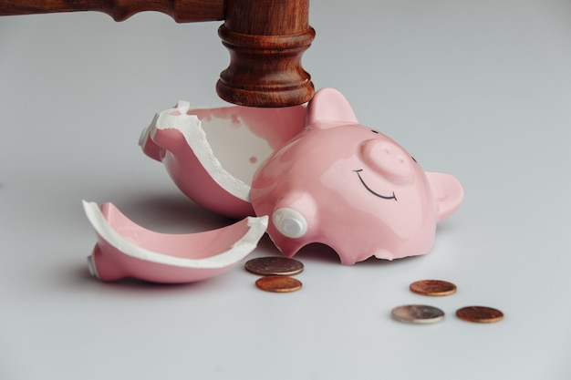 Broken piggy bank with coins and wooden judge gavel