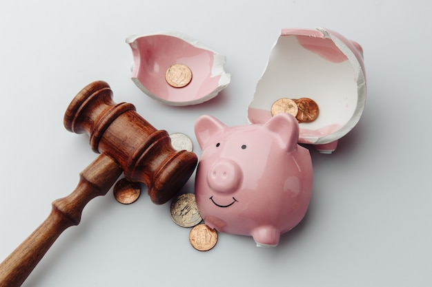 Broken piggy bank with dollar bills, coins and wooden gavel on a white table.