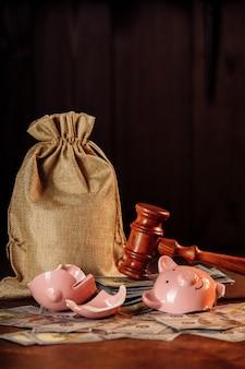 Разбитая копилка с денежным мешком и молотком судьи. концепция инвестиций и банкротства.