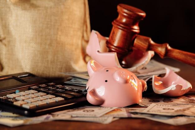 Broken piggy bank with money bag and judge gavel closeup economy concept