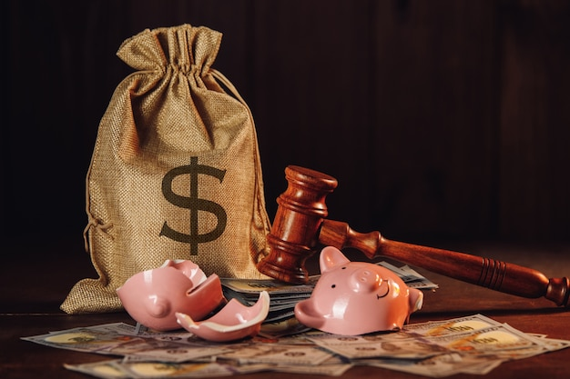 Broken piggy bank with money bag and judge gavel. economy concept.