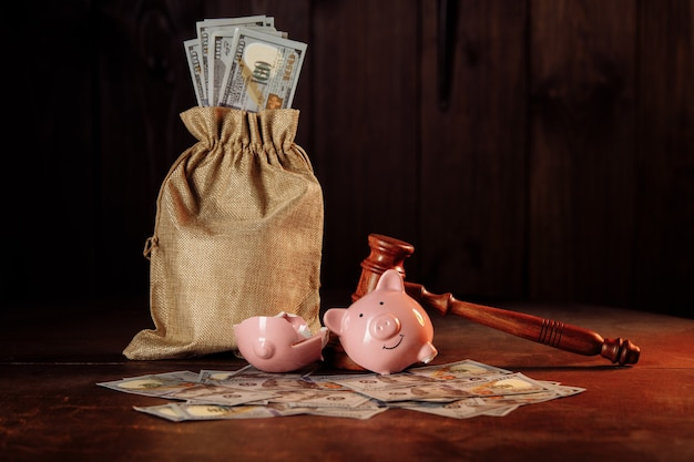 Broken piggy bank with money bag and judge gavel investment and bankruptcy concept