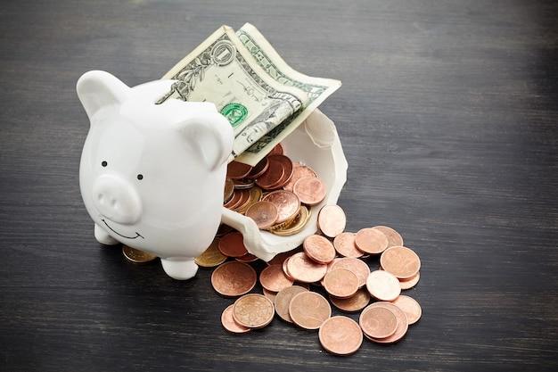 Broken piggy bank with money on dark wooden background