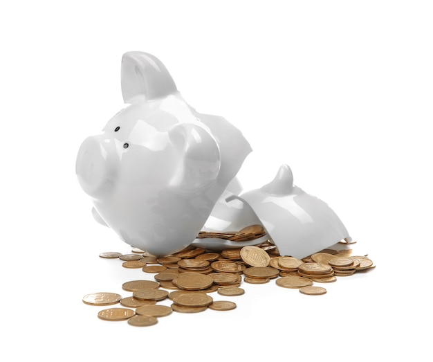 Broken piggy bank with money on white surface