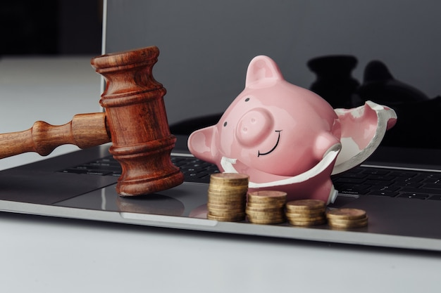 Broken piggy bank with stack of coins and wooden gavel. business, finance and bankruptcy concept