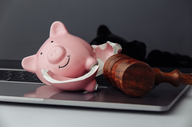 Broken piggy bank and wooden gavel on keyboard close-up. business, finance and bankruptcy concept