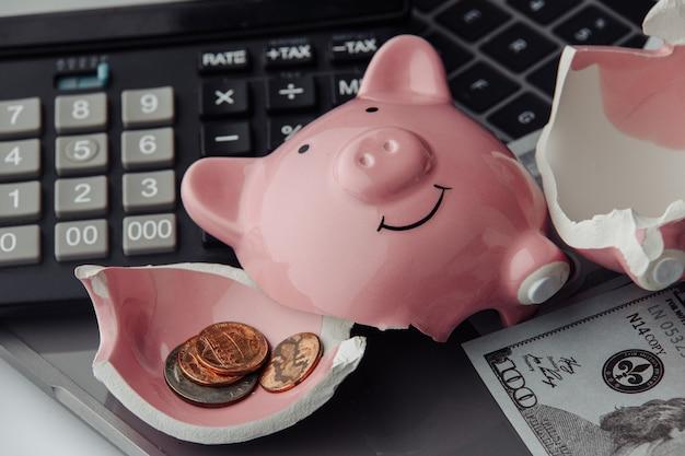 키보드에 깨진 된 돼지, 계산기 및 달러 지폐