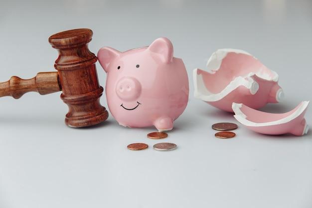 Сломанная копилка с монетами и деревянным молотком. концепция бизнеса и банкротства