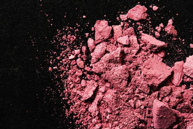 Broken pink blush on black table