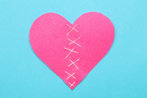 Broken pink heart on a bright blue background.