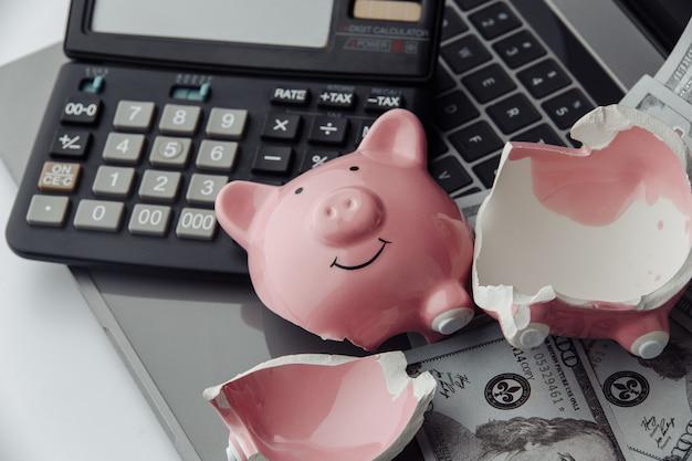 Сломанная розовая копилка, калькулятор и долларовые купюры на ноутбуке. концепция финансов и банкротства