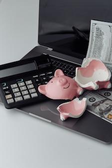 Сломанная розовая копилка на клавиатуре, калькуляторе и долларовых купюрах. концепция финансов и банкротства. вертикальное изображение