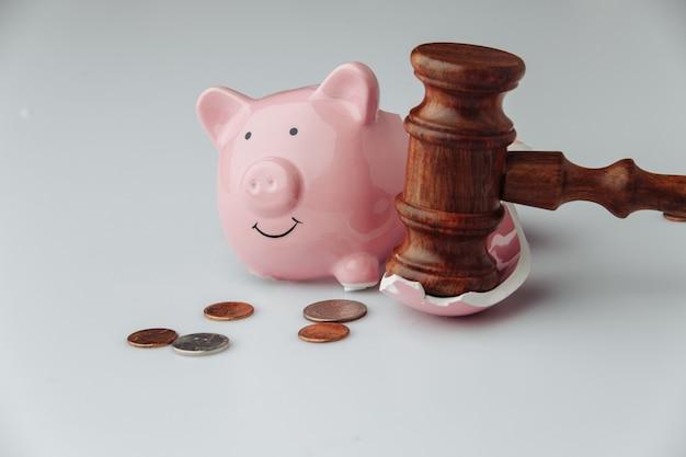 Сломанная розовая копилка с монетами и деревянным молотком судьи на белом фоне. концепция финансов или банкротства