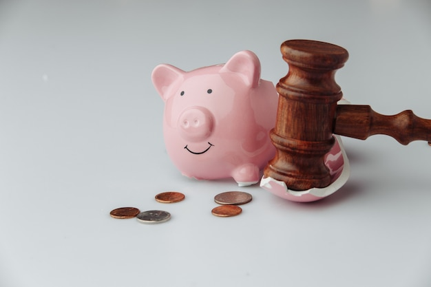 Broken pink piggy bank with coins and wooden judge gavel on a white background.