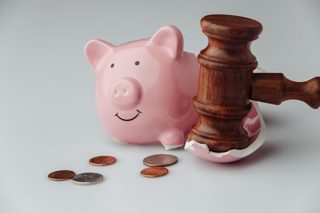 Broken pink piggy bank with coins and wooden judge gavel on a white