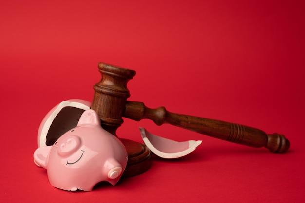빨간색 배경에 나무 판사 망치가 있는 깨진 분홍색 돼지 저금통. 법률 및 파산 개념
